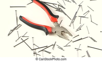 Gray and red pliers on white among nails, rotation - Open...