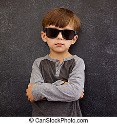 Little boy wearing sunglasses posing with his arms crossed -...