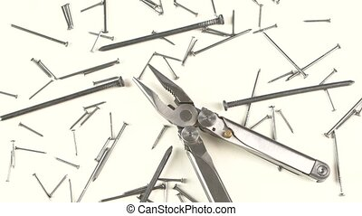 Metal round-nose pliers among nails on white, rotation -...