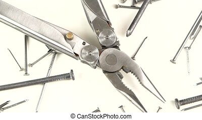 Metal round-nose pliers among nails on white, rotation,...