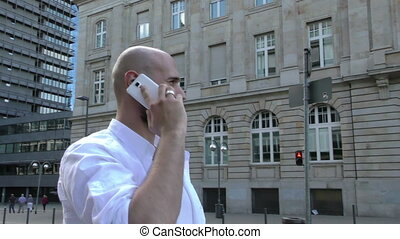 Man Talking with Cellphone in City near Traffic and Business...