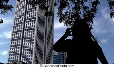 Woman Silhouette Talking with Cellphone and Business Tower