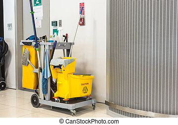Yellow mop bucket and set of cleaning equipment in the...