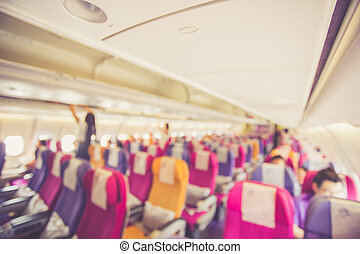 Blurred image Interior of airplane with passengers on seats,...