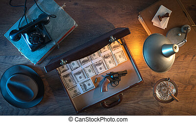 Dollar packs and gun - Vintage desktop in the dark with a...