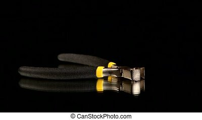 Wire cutters with yellow, gray handle on black, reflection,...