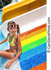 Child in bikini sliding water park - Girl in yellow bikini...