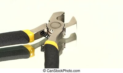 Part of wire cutters with yellow, gray handle on white,...