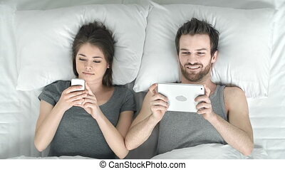 Bedtime Fun - Above view of adult couple playing videogames...