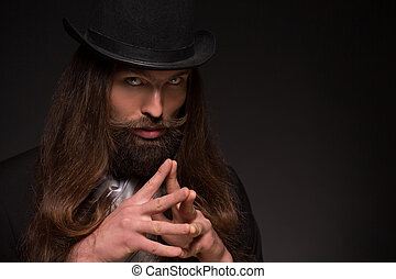 Magician - Serious long-haired magician thinking about...