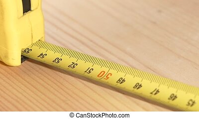 Tape measure, roulette reeling, slow motion - Yellow tape...