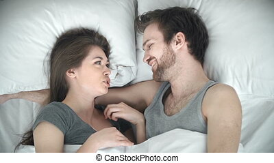Bedtime Stories - Above view of couple chatting in bed
