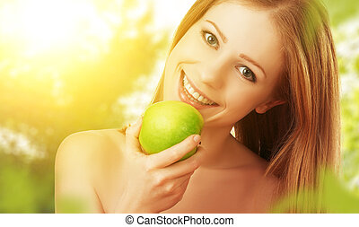 beautiful young woman eating green apple in the summer on the nature