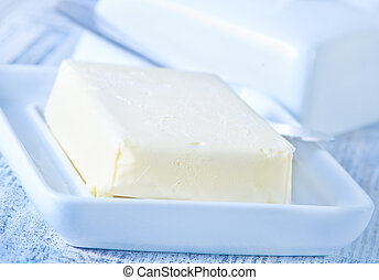 fresh butter on plate and on a table