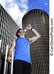 young sport man drinking water bottle after running training...