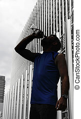 silhouette of young sport man drinking water bottle after...