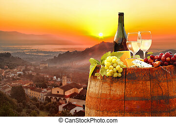 White wine with barrel against colorful sunset in Chianti,...