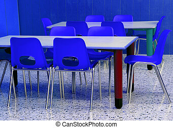 classroom of a kindergarten with blue chairs without...