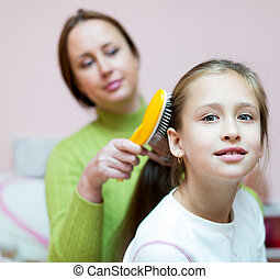 mother combing her daughters hair - Adult mother brushing...