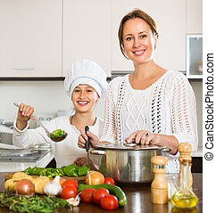 Mother and daughter cooking together - Smiling mother and...