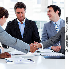 Close-up of successful business people closing a deal in a...