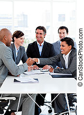 Successful international business people shaking hands in...
