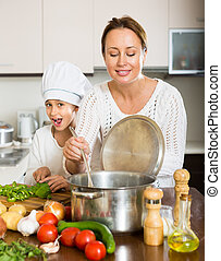 Mother and daughter cooking together - Positive mother and...