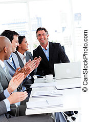 Team of successful business people clapping in a meeting