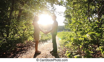 Silhouette couple kissing over sunset background in park