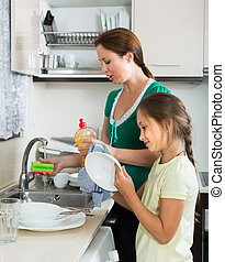 Girl helping mother washing dishes in the kitchen Focus on...