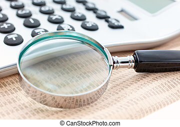 financial newspaper with calculator and magnifier. Closeup....