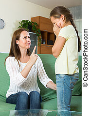 Mother berating  crying daughter
