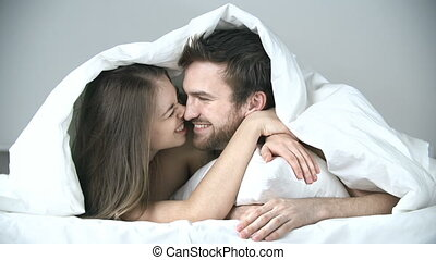 Nuzzling Up - Close up of sweet couple cuddling in bed