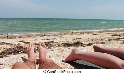 The legs of two people are sunbathe on the beach by the sea....