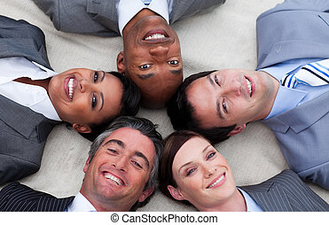 Multi-ethnic business team lying on the floor with heads...