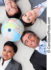 Smiling business team holding a terrestrial globe with heads...