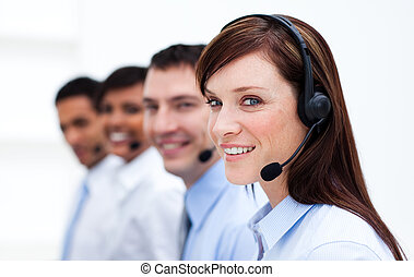 Business team with headset on working in a call center and...