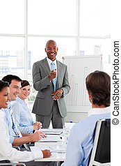 Confident Afro-American businessman discussing with his team...