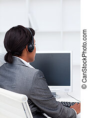 Smiling businesswoman working at a computer in a call center