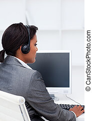 Serious businesswoman working at a computer with headset on