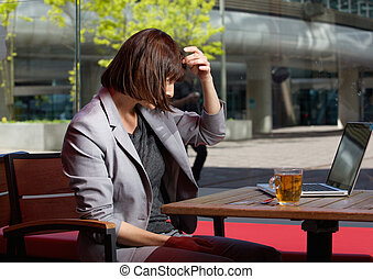 Business woman adjusting her hair and looking at laptop -...