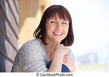 Attractive older woman smiling - Close up portrait of an...