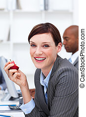 Portrait of a smiling businesswoman eating an apple in the...