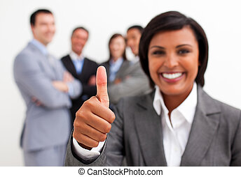 Attractive female executive smiling at the camera with thumb...