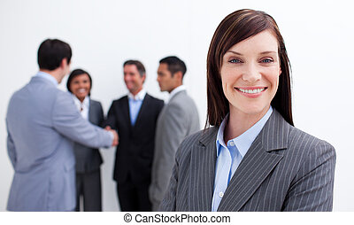 Smiling female executive with her team in the background