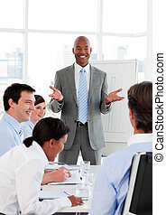 Smiling businessman doing a presentation to his colleagues...