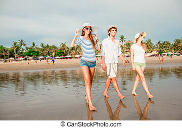 Group of happy young people walking along the beach on...
