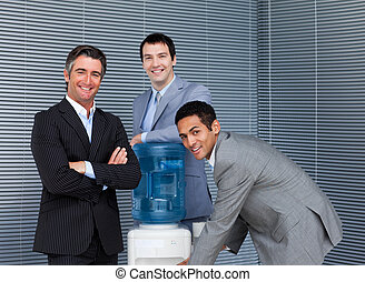 Multi-ethnic business team at water cooler in the office