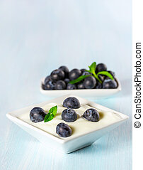 Yogurt with ripe blueberries on a wooden background