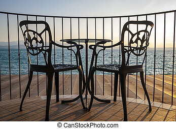 Terrace lake view with iron chairs and table